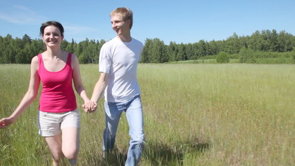 man and woman holding hands also run forward across field