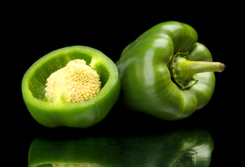 Closeup halved green bell peppers isolated on black