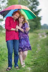 Pregnant couple under an umbrella