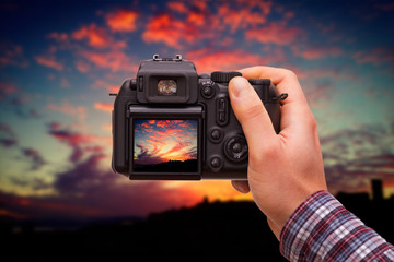 DSLR camera in hand shooting colorful sunset