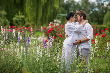 Happy pregnant couple hugging in nature