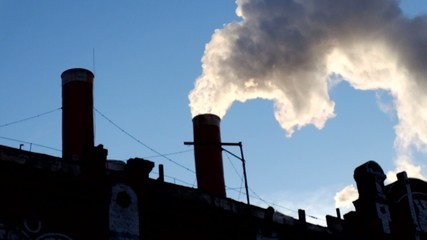 Backlit of the working power plant with smoke from chimney in a