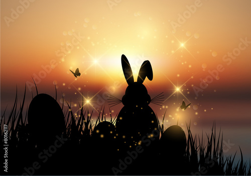 Easter bunny sat in grass against a sunset sky - 80162117