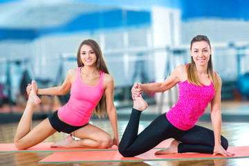 Young attractive girls do yoga.
