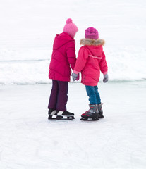 girls with ice skates with reflection on winter ice