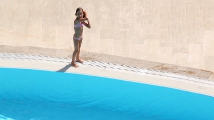 Little girl climbs out of pool and then jumps into water again