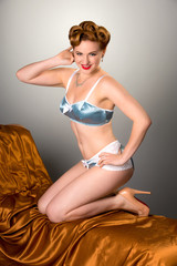 Fifties styled beautiful redheaded woman in satin lingerie