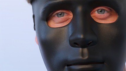 man in black mask on face turns from profile full face close up