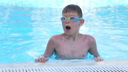 Boy in swimming glasses dives his head under water in the pool
