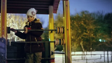 Little girl in warm clothes plays on playground at winter