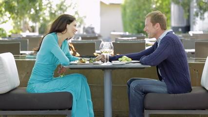 Couple enjoying a gourmet dinner outdoors at a luxury resort