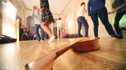 Wooden guitar lies on floor and young people dance in hall