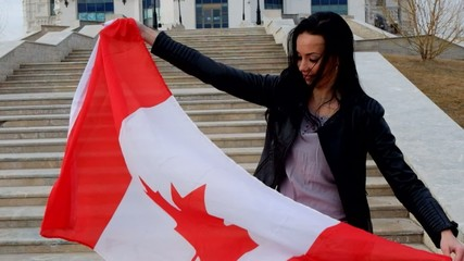 Portrait of a brunette girl with Canadian flag  outdoors