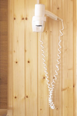 White hair dryer hanging on wooden wall