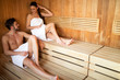Young and beautiful couple relaxing in a sauna