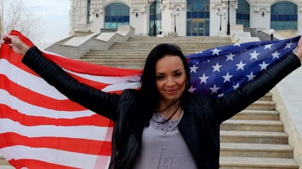 Proud american girl holding stars and stripes  flag outdoors