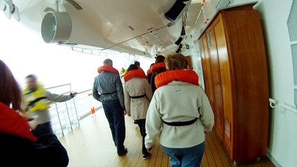 Crowd of people go on liner deck in life jackets