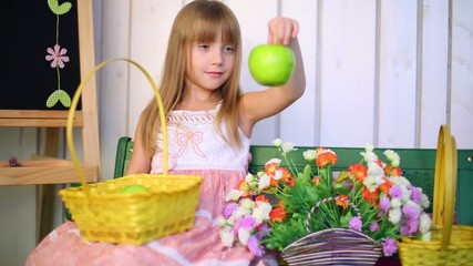 Little girl takes an apple from the basket and looks at it