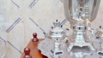 Three retro russian samovars on silver tray at wooden table