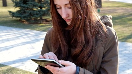 Redhead teen girl using tablet PC outdoors full HD footage