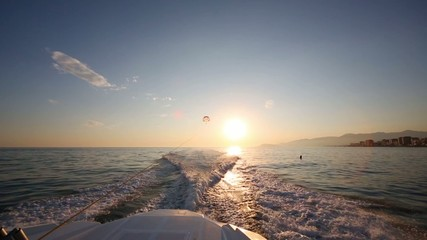 Glider flies over sea at evening and traces of boat on water