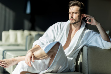Young, handsome man in the morning thinking in a robe