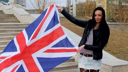 Smiling latina brunette holding Union Jack flag waving by the