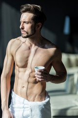 Handsome, muscular, young man drinking his morning coffee