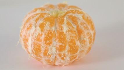 Peeled orange fresh tasty tangerine circling closeup