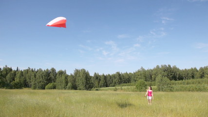 girl in field keeps rope from kite highly