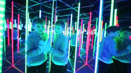 Boy moves his back forwards in mirror labyrinth