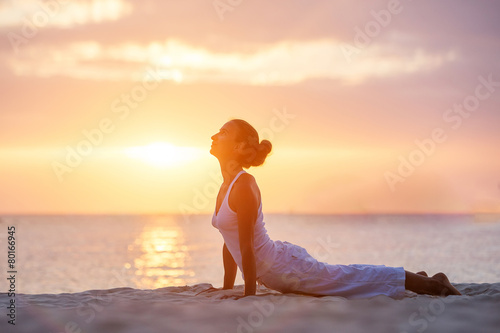 Foto op Canvas Gymnastiek Caucasian woman practicing yoga at seashore