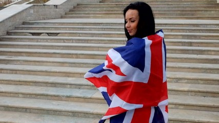 Sexy brunette warped in UK Union Jack flag waving by the wind.