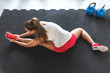 Woman worming up and stretching her body at the gym - 80167374