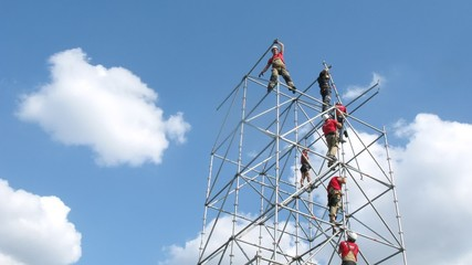 Team of climbers mounts tower against sky