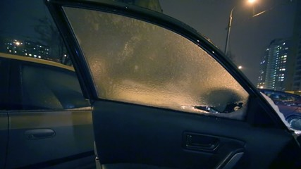 Male hand breaks ice on window of car door after icy rain