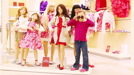 girl stands next to mannequins in clothing store and imitate it