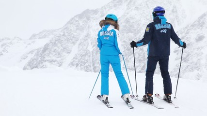 Man and woman skier stands on hillside of mountain