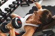 Woman lifting  weights and working on her chest at the  gym
