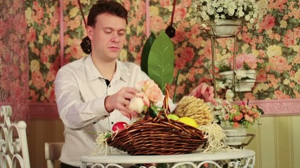 Man sits at table with beautiful flowers in basket