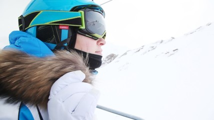 Woman skier in goggles goes up in chairlift to ski route.
