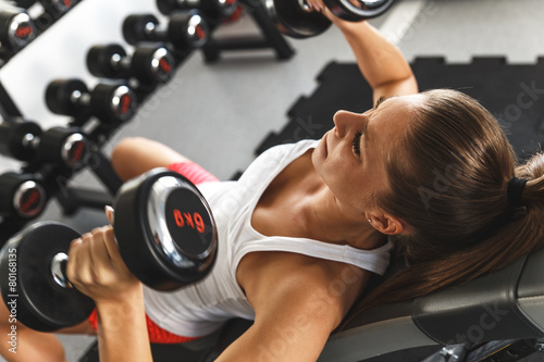 Woman lifting  weights and working on her chest at the  gym Poster
