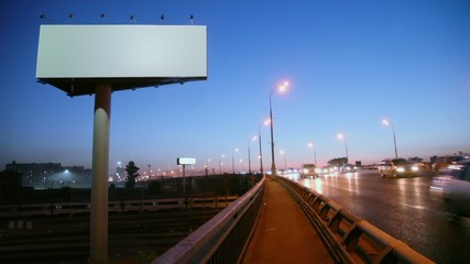 Empty advertising billboard on sidelines of road with traffic near railroad at evening, fast motion time lapse