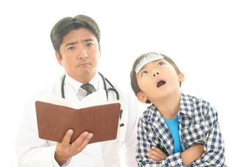体調不良の男の子と診察する医師