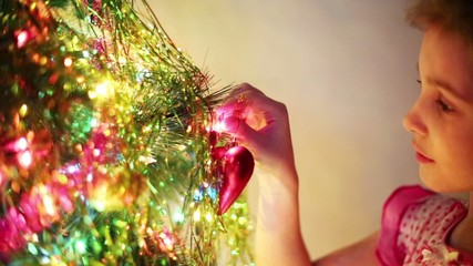 Beautiful girl decorates Christmas tree by toy heart at evening