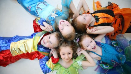 children in costumes sit on floor in star shape holding hands