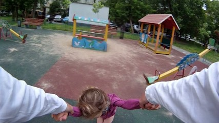 Father twist the daughter by hands at playground
