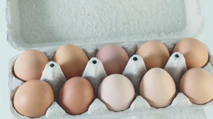 Ten brown eggs in cardboard  container circling closeup