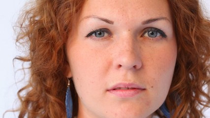 face of red-haired woman in blue drops close up