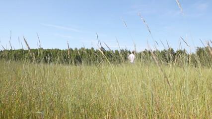 guy blonde in jeans runs across field in grass to wood